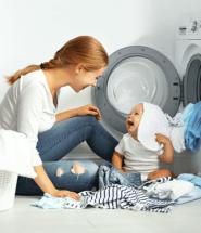 Matka s dieťatkom perie oblečenie v práčke