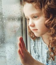 Dievča pri okne pozoruje dážď